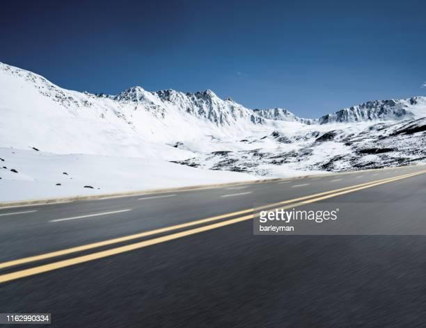 highway beside snow mountain - 深い雪 ストックフォトと画像