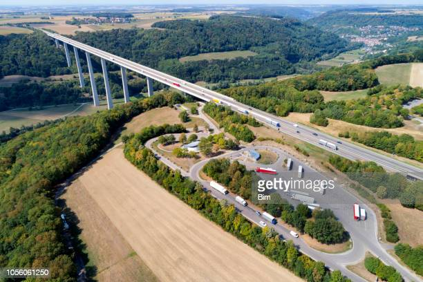 Highway bridge with trucks and rest area, aerial view