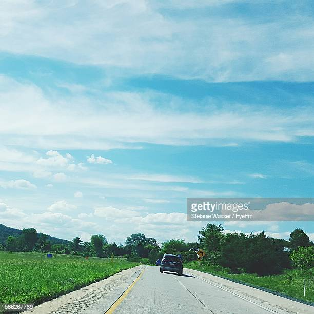 highway by field against cloudy sky - wasser stock pictures, royalty-free photos & images