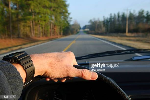 Highway driving with hand on steering wheel on two-lane road