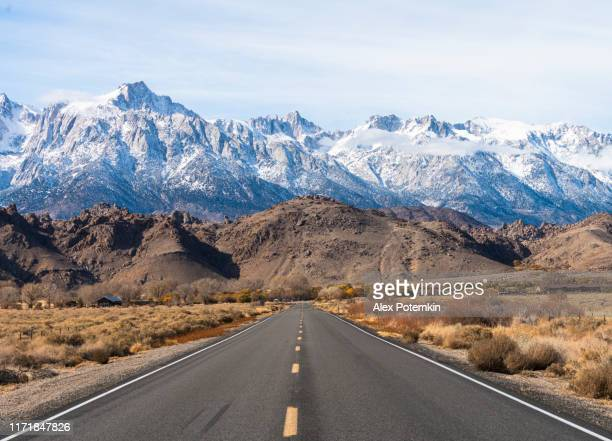 highway heading toward sierra nevada mountains covered by snow.  california, usa - mountain stock pictures, royalty-free photos & images