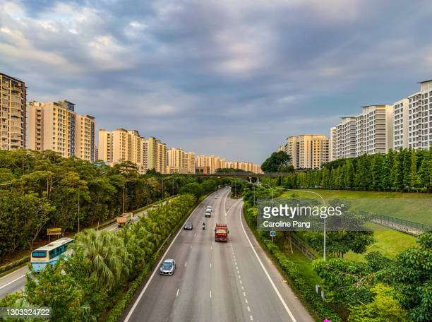 highway in between a stretch of high rise residential buildings. - between stock pictures, royalty-free photos & images