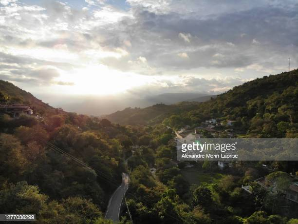 highway in the middle of trees and houses, buildings surrounded by the green mountains at sunset in san gil / colombia -  キリスト教 伝来の地  ストックフォトと画像