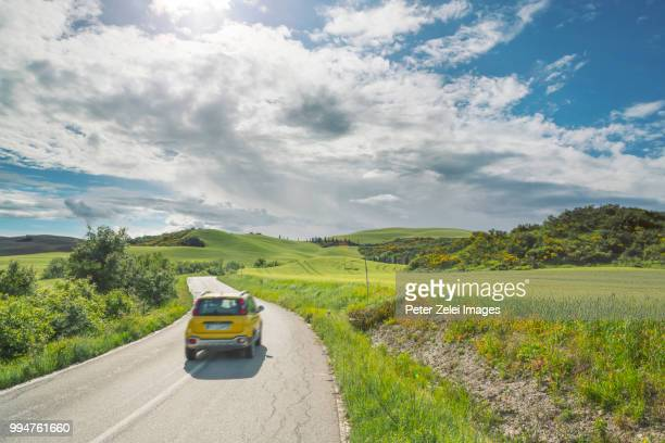 highway in tuscany with a motion blurred car - rushing the field stock pictures, royalty-free photos & images