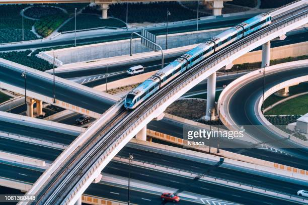 highway intersection and metro train in dubai, uae - built structure stock pictures, royalty-free photos & images