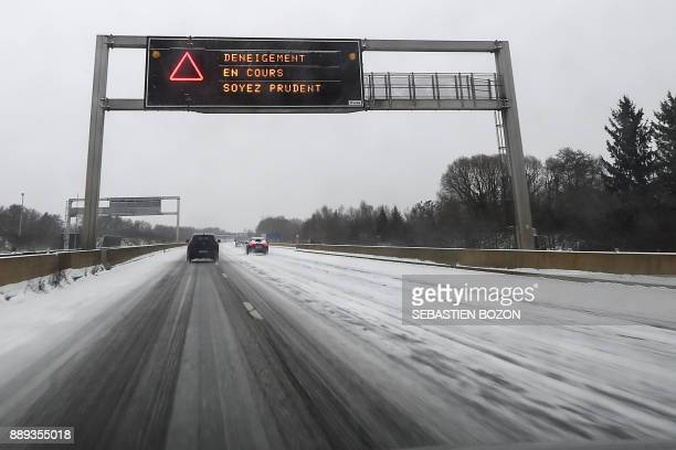 A highway panel reading 'Be careful snowclearing in progress' is pictured on the A36 highway between Montbeliard and Besançon on December 10 2017 /...