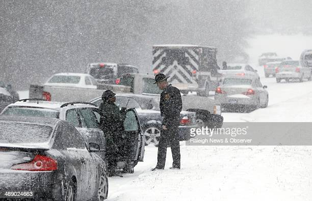 A Highway Patrol officer checks on a stranded motorist on Hammond Road in Raleigh NC Wednesday Feb 12 2014 as snow pounds the Triangle