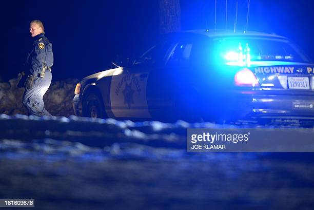 A highway patrol officer guards a roadblock on Highway 38 near Angeles Oaks during a standoff with fugitive excop Christopher Dorner near San...