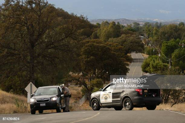 A Highway Patrol officer speaks to a woman while blocking off a road to traffic after a shooting on November 14 in Rancho Tehama California Four...