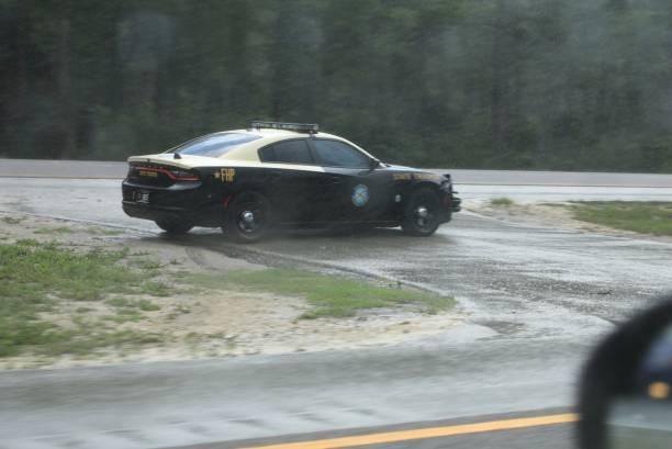 Highway patrol vehicle watching for speeding motorists in a rain storm