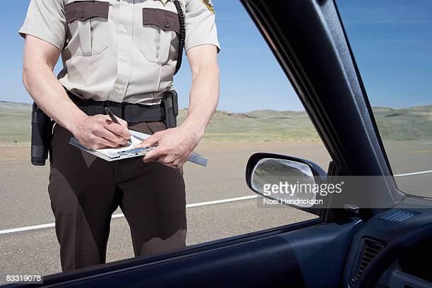 highway patrolman writing ticket - bestrafung stock-fotos und bilder