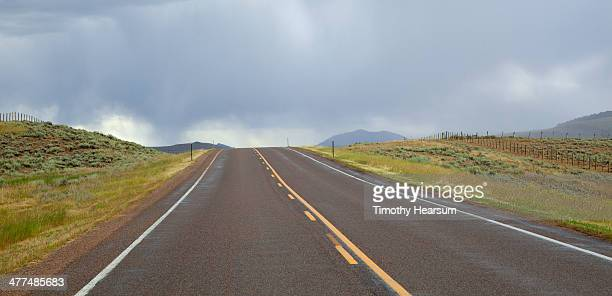 highway through ranch land; storm clouds beyond - timothy hearsum stock photos and pictures