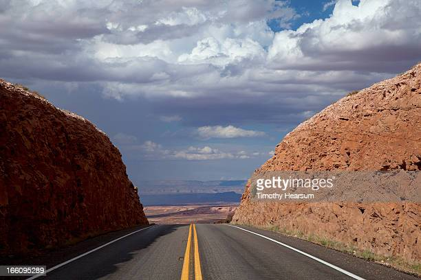 highway through steep road cut with view beyond - timothy hearsum stock photos and pictures