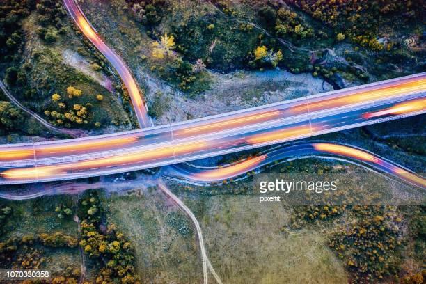 snelweg viaduct over een gebogen landweg in bosrijke omgeving - tijdopname stockfoto's en -beelden