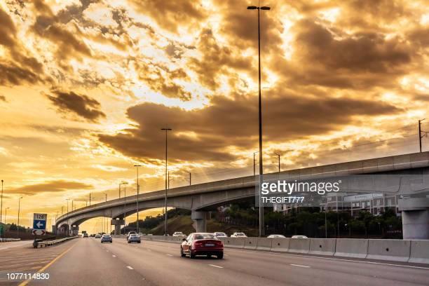 n1 snelweg met gautrain metro brug onder storm wolken - centurion zuid afrika stockfoto's en -beelden