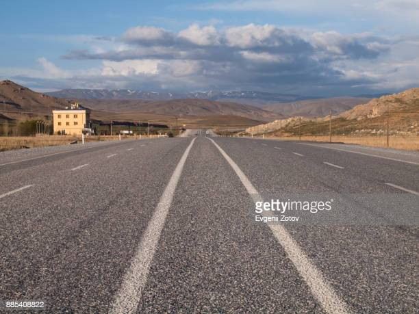 highway with mountain background and dramatic sky in van province, eastern anatolia, turkey - en medio de la carretera fotografías e imágenes de stock