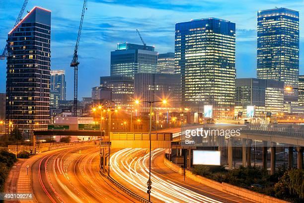Autobahn-Verkehr in der Abenddämmerung und Canary Wharf, London Skyline
