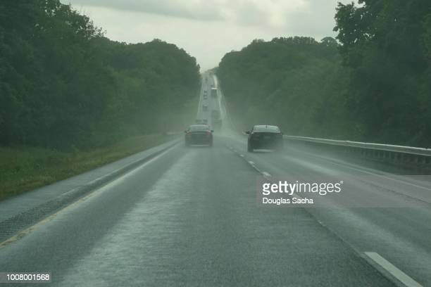 highway with vehicles in the rain - dashboard camera point of view stock photos and pictures