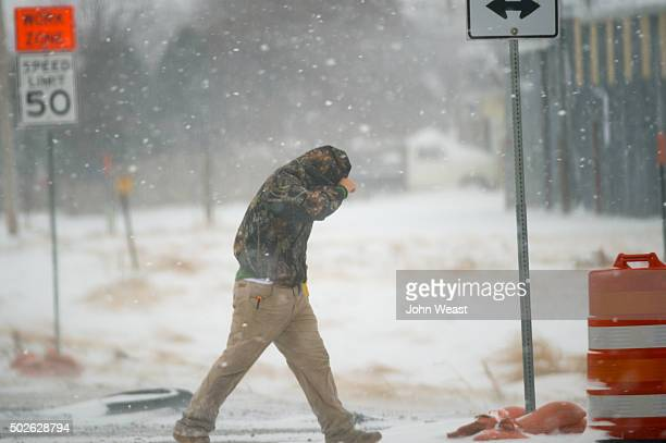 A highway worker tries to shield himself while walking to his truck on December 27 2015 in Lubbock Texas Coming on the heels of several strong...