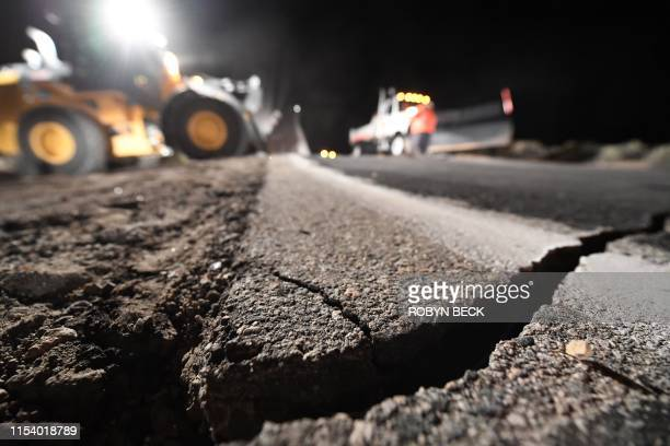 Highway workers repair a hole that opened in the road as a result of the July 5, 2019 earthquake, in Ridgecrest, California, about 150 miles north of...