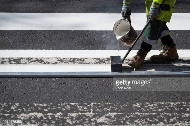 Highways Maintenance worker takes advantage of the COVID19 coronavirus lockdown and quiet streets to repaint the iconic Abbey Road crossing on March...