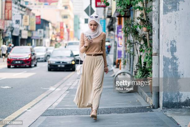 hijab businesswomen using phone while walking - malaysia stock pictures, royalty-free photos & images