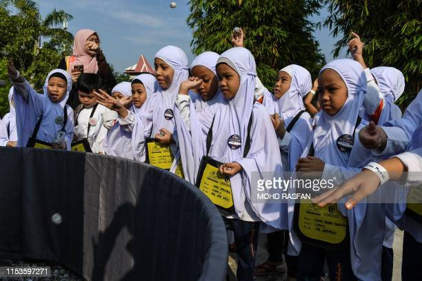 Hijabclad Muslim girls throw mock stones made from papier mache during the ritual of stoning the devil during an educational simulation of the Hajj...