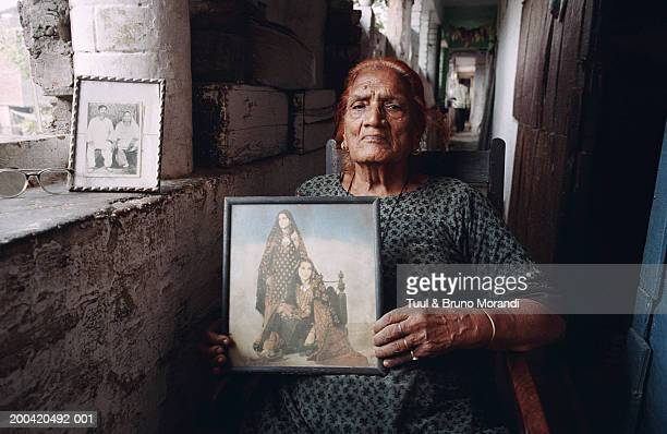 Hijra in chair holding photograph of self when young, portrait