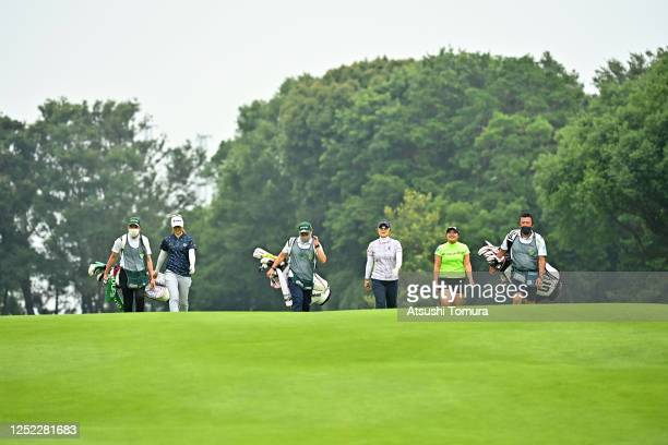 Hikari Kawamitsu Saiki Fujita and Ai Suzuki of Japan and their caddies walk with keeping distance during the first round of the Earth Mondamin Cup at...
