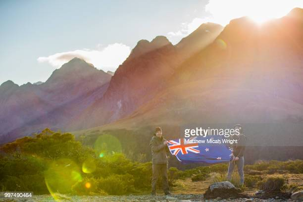 a hike through the key summit track as part of the routeburn track in the fiordland national park. people pose with the new zealand national flag. - new zealand flag stock photos and pictures