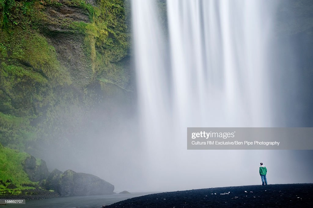 Hiker admiring giant waterfall : Stock Photo