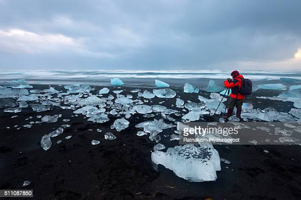 hiker admiring glaciers on beach reflecting sunrise sky - jokulsarlon lagoon stock photos and pictures