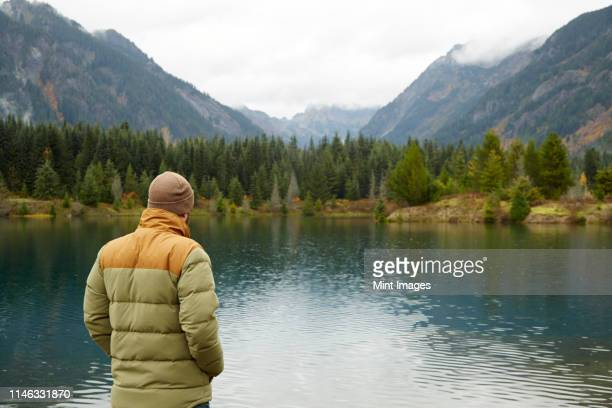hiker admiring lake and remote landscape - coat stock pictures, royalty-free photos & images
