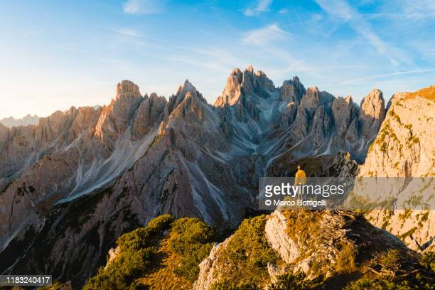 hiker admiring the dolomites at sunrise, italy - reportaje imágenes stock pictures, royalty-free photos & images