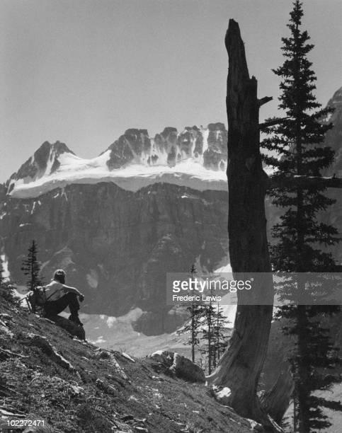 A hiker admiring the mountain view near Moraine Lake Alberta Canada circa 1955