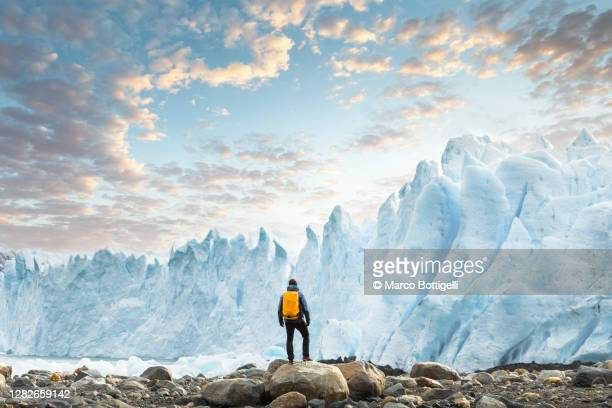hiker admiring the perito moreno glacier at sunset, argentina - argentina stock pictures, royalty-free photos & images