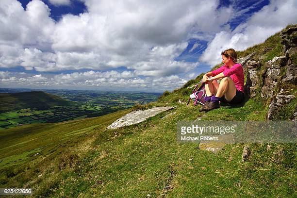 hiker admiring the views across the black mountains in the brecon beacons national park in wales - crickhowell foto e immagini stock