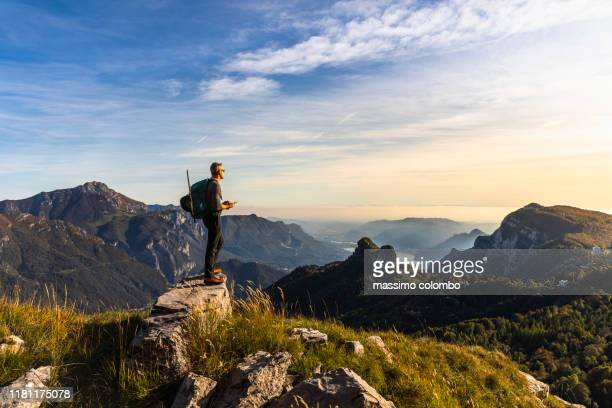 hiker alone looking at view from mountain top - vetta foto e immagini stock