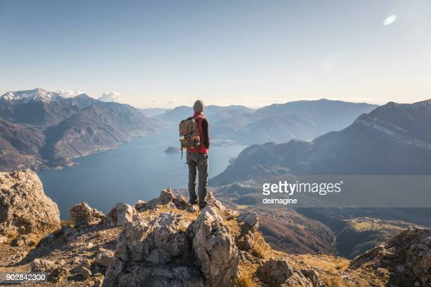 hiker alone on top of the mountain - mountain peak stock pictures, royalty-free photos & images