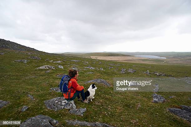 Hiker and dog looking out across moorland