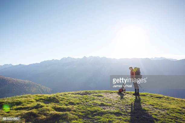 Hiker and rescue dog on grassy hill, Switzerland