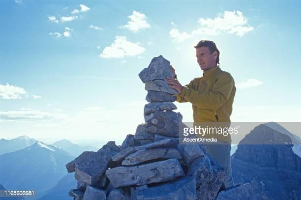 日の出の山頂でハイカーと石のケアン - 石塚 ストックフォトと画像