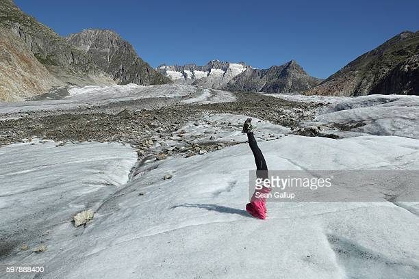 Hiker and yoga enthusiast Karin Bittel who was participating in a guided tour across the Aletsch glacier stands on her head on the ice of the glacier...