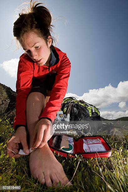 hiker applying bandage to blister - first aid kit stock pictures, royalty-free photos & images