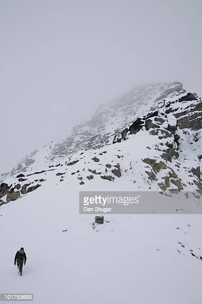 A hiker approaches a snowy peak covered in fog in British Columbia, Canada.