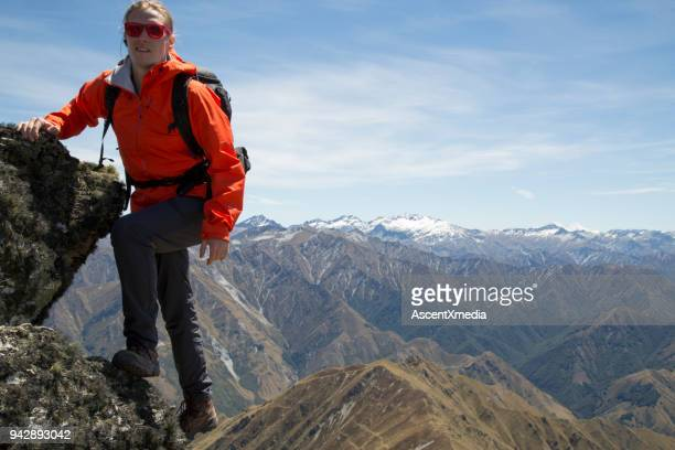 hiker approaches summit above mountains - striding stock pictures, royalty-free photos & images