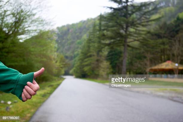 hiker asking for lift on road - cliqueimages stockfoto's en -beelden