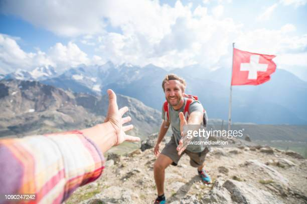 hiker assisting teammate at mountain top giving a helping hand to reach summit, switzerland - switzerland stock pictures, royalty-free photos & images