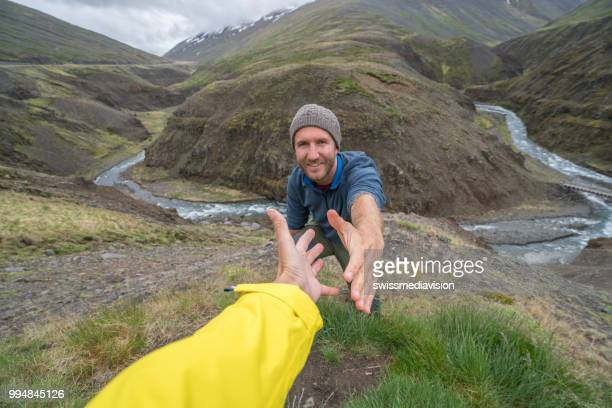 Hiker assists teammate to reach mountain top above canyon in Iceland