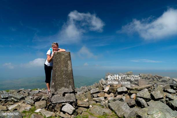 hiker at a trig point in the black mountains, brecon beacons national park, wales. - crickhowell foto e immagini stock